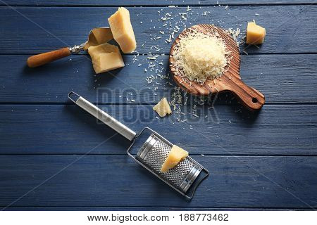 Wooden board with cheese and grater on table