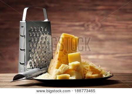 Composition with different types of cheese and graters on wooden table
