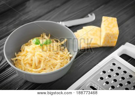 Bowl with cheese and grater on wooden table