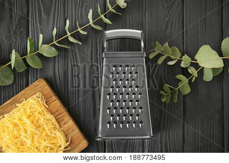 Grater and cheese on  wooden table