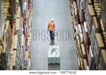 Loader pulling forklift while moving along aisle between shelves with boxes