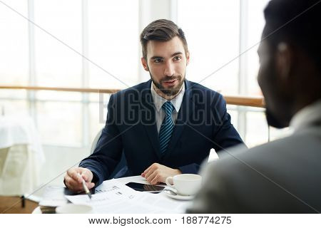 Portrait of two businessmen, one of them African, negotiating conditions while discussing deal during meeting in cafe