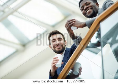 Portrait of handsome bearded businessman with African-American colleague looking down from glass balcony and smiling holding cups during break