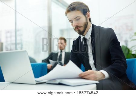 Serious economist looking through financial papers at workplace