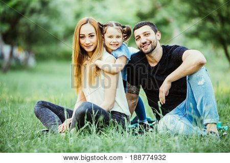 Young Happy Family In Summer Park. Father And Mother Spend Time In Summer Park With Their Daughter W