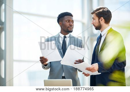 Two economists with papers having conversation