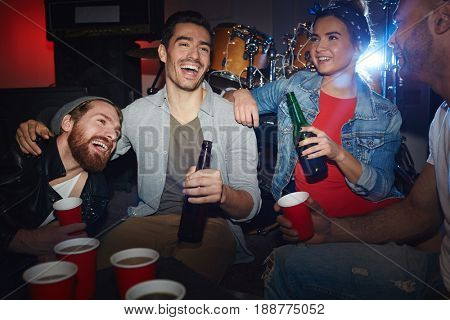 Ecstatic friends with beer having fun in night club