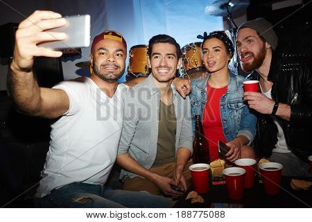 Group of cheerful buddies posing for selfie at party