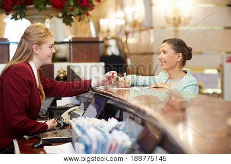 Senior female filling in registration form at reception