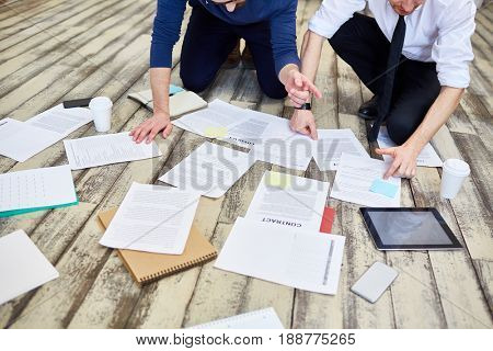 Assorted documents and contracts laid out on wooden office floor with hands of two unrecognizable  business people working