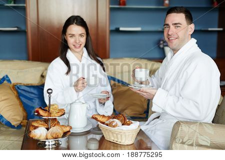 Young couple in bath-robes having tea in the morning