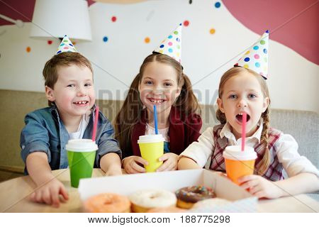 Little buddies in birthday-caps enjoying party