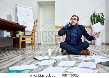 Portrait of bearded man speaking by phone looking troubled and sorting documents sitting on floor in office