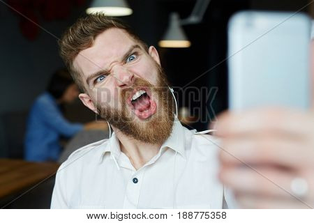 Portrait of modern bearded man yelling and grimacing angrily to camera posing for selfie photo
