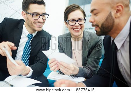 Portrait of modern business people one woman and two men smiling cheerfully while discussing work in meeting