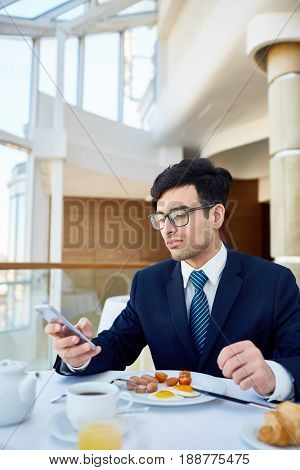 Busy leader texting in smartphone at lunch break