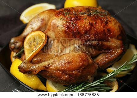Homemade baked chicken with lemon and rosemary on table, closeup