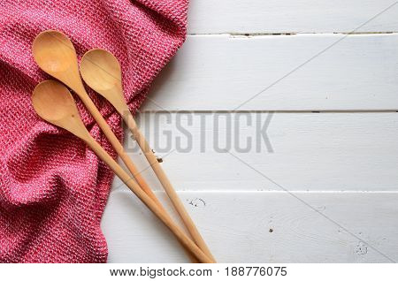 Three wooden mixing spoons and red dish towel on a white wooden table top.