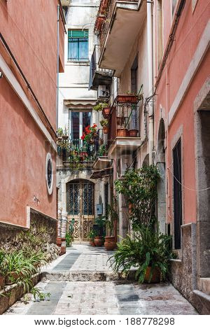 TAORMINA, SICILY, ITALY - APRIL 27, 2017: Narrow cobbled lane between colourful red walls, with balconies, geraniums and green potted plants in Taormina, Sicily, Italy
