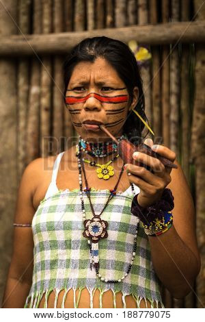 Native Brazilian woman from Tupi Guarani tribe smoking pipes, Brazil