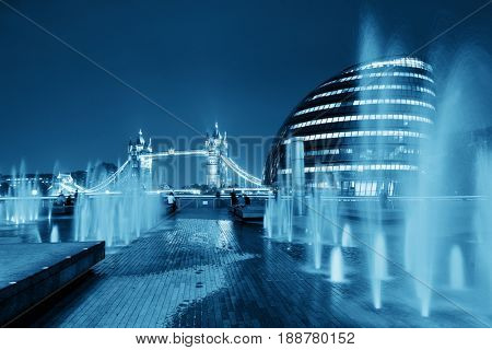 London Tower Bridge, City Hall and fountain at night in business district.