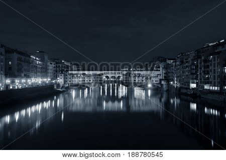 Ponte Vecchio over Arno River at night in Florence Italy monochrome.
