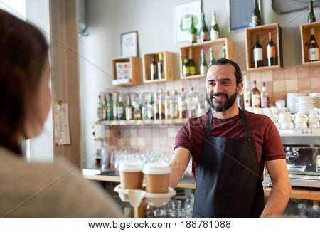 small business, people, takeaway and service concept - happy man or waiter giving paper cup with hot drink to customer at coffee shop