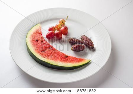 Black grapes, sweet date fruits with watermelon slice served on the white plate. A nutritious and healthy Ramadan snack for iftar beginning.