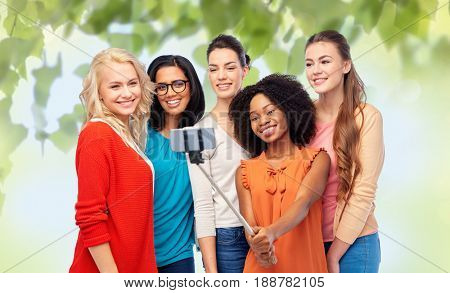 diversity, race, ethnicity, technology and people concept - international group of happy smiling different women taking picture with smartphone on selfie stick over green natural background