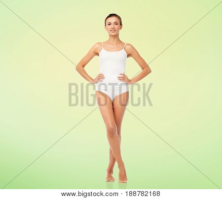 beauty, people and bodycare concept - beautiful young woman in white underwear over green natural background