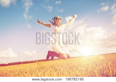 happiness, nature, summer holidays, vacation and people concept - smiling young woman in wreath of flowers and gumboots jumping on cereal field