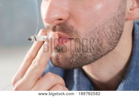Handsome man smoking cigarette, closeup