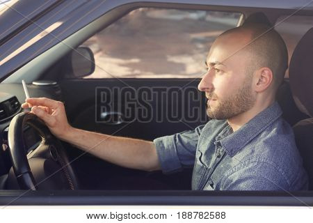 Handsome man smoking cigarette in car