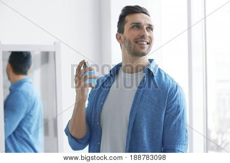 Handsome man using perfume at home