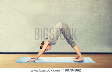 fitness, sport, people and healthy lifestyle concept - woman making yoga in downward facing dog pose on mat over gym room background