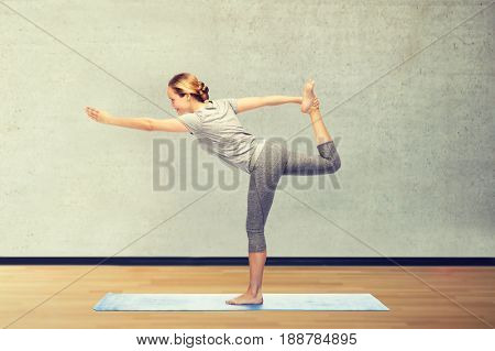 fitness, sport, people and healthy lifestyle concept - woman making yoga in lord of the dance pose on mat over gym room background
