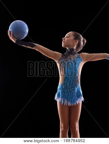 Rhythmic gymnastic little girl holding a blue ball.