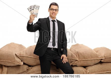 Businessman holding bundles of money in front of a pile of burlap sacks isolated on white background