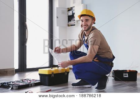 Young electrician checking drawings near toolboxes in light room