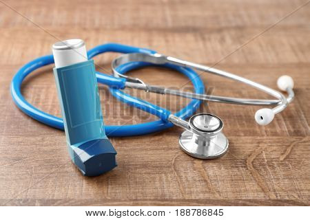 Asthma inhaler with stethoscope on wooden table