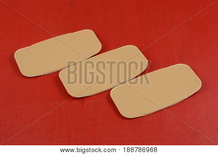 Three large first aid adhesive bandages on red background