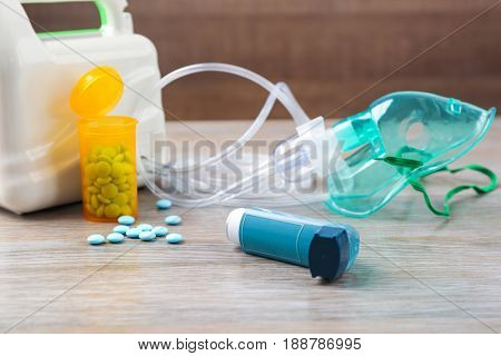 Asthma inhaler, pills and nebuliser on wooden table