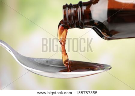 Pouring cough syrup into spoon on blurred background
