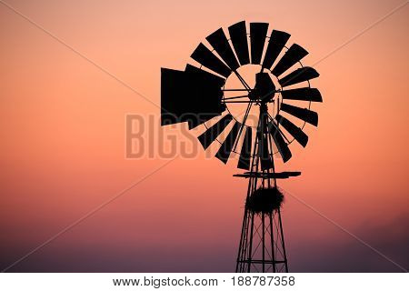 A windmill silhouetted against a red sunset