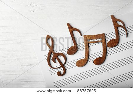 Musical notes lying on music sheet on white wooden background
