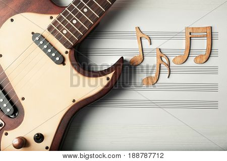 Musical notes, sheet and guitar on white wooden background, closeup