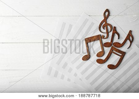 Musical notes lying on music sheets on white wooden background