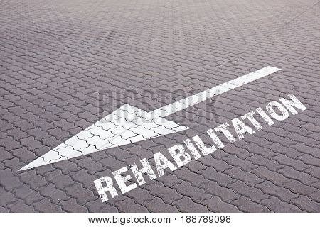 Recovery concept. Arrow pointing way to REHABILITATION on pavement outdoor