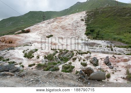 Mineral water stream covered the slope with travertine deposits, Cross Pass, Gudauri, Georgia.