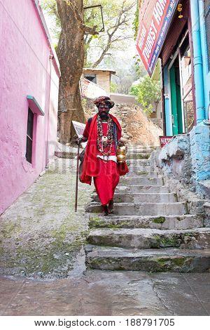LAXMAN JHULA, INDIA - APRIL 20, 2017: A Hindu sadhu walking in the streets in Laxman Jhula on the 20th april 2017 in India